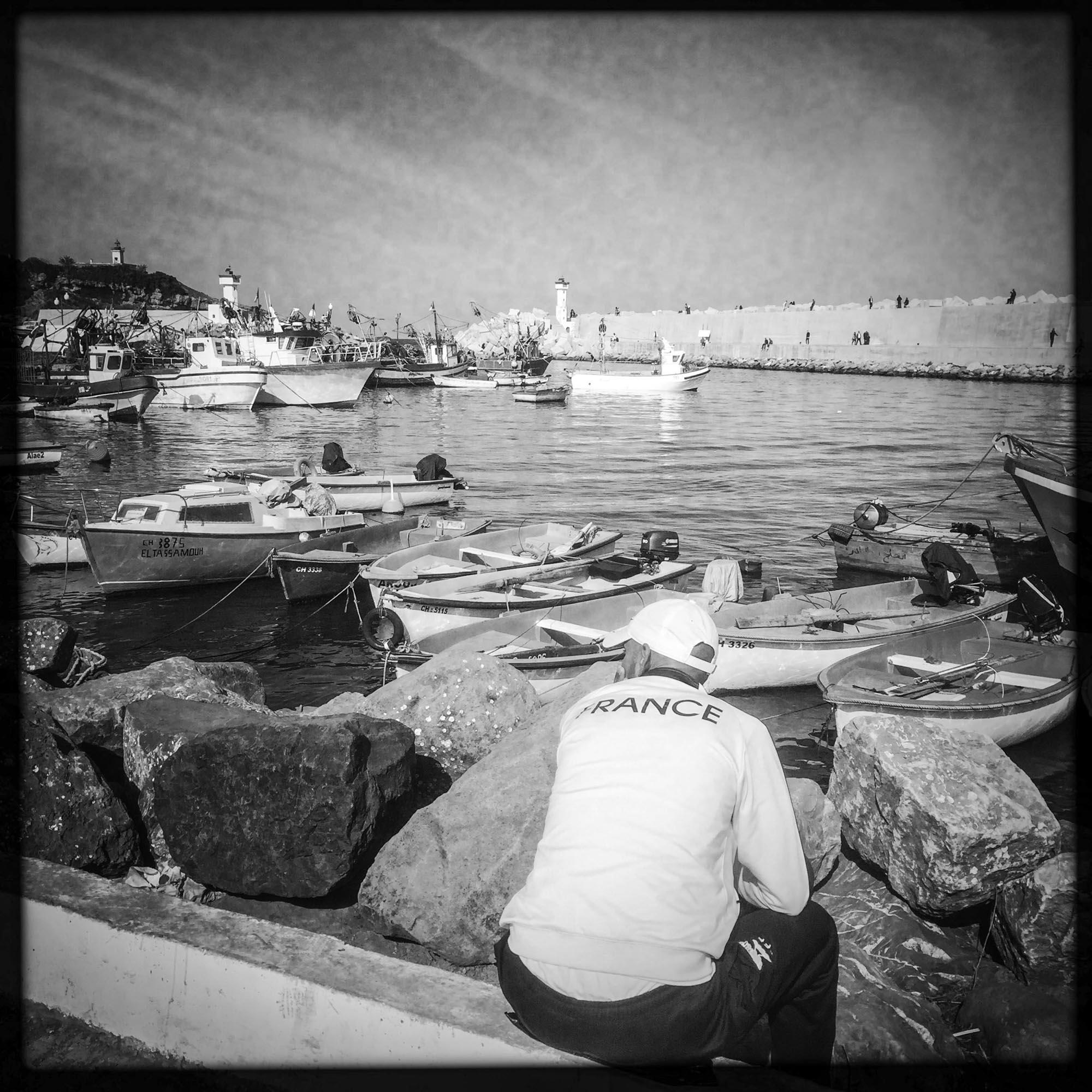 Un homme assis dans le petit port de Tipaza. 31/06/2016, Tipaza-ALGER.