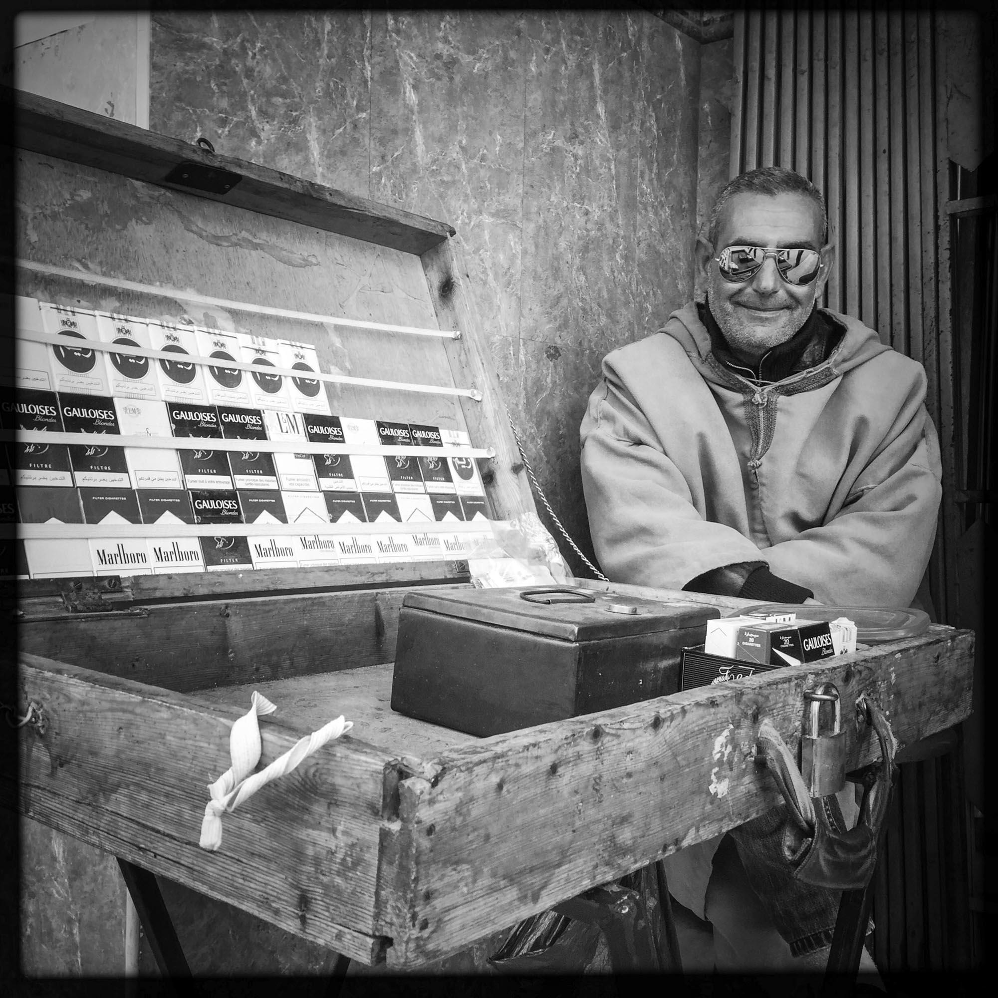 Un vendeur de cigarettes devant un café. 13/02/2016, Guelma-Algérie.