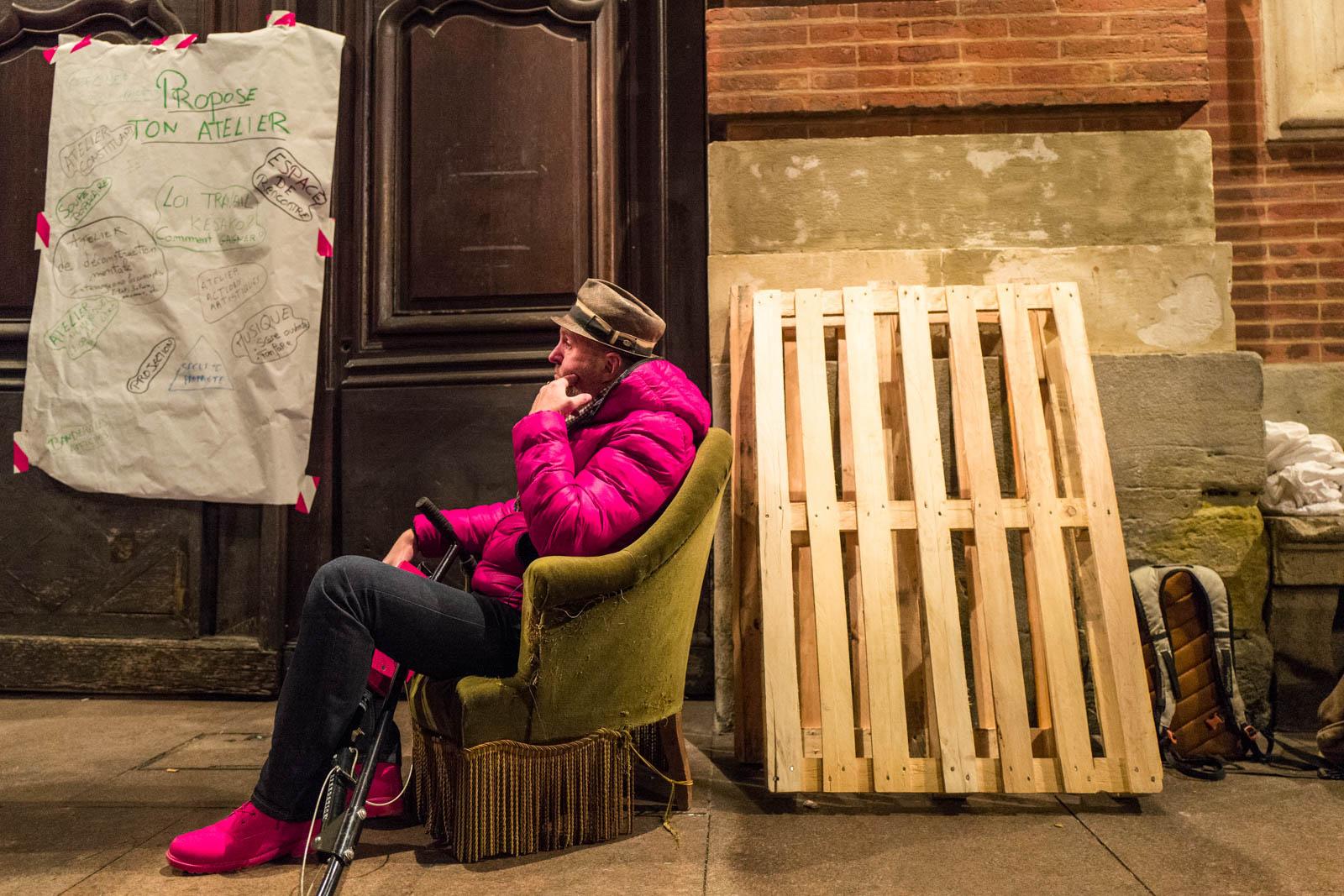 Un homme cogite seul sur son fauteuil lors du rassemblement NUIT DEBOUT sur la place du Capitole. Depuis le 31 mars des personnes se sont installées sur différentes grandes places dans des villes de l'hexagone.  Ces rassemblements pacifiques, appellés NUIT DEBOUT sont ouverts et populaires, ils visent à réinvestir l'espace public pour échanger, débattre et construire, la Place du Capitole est occupée depuis le 5 avril. 6/04/2016, Toulouse-France.