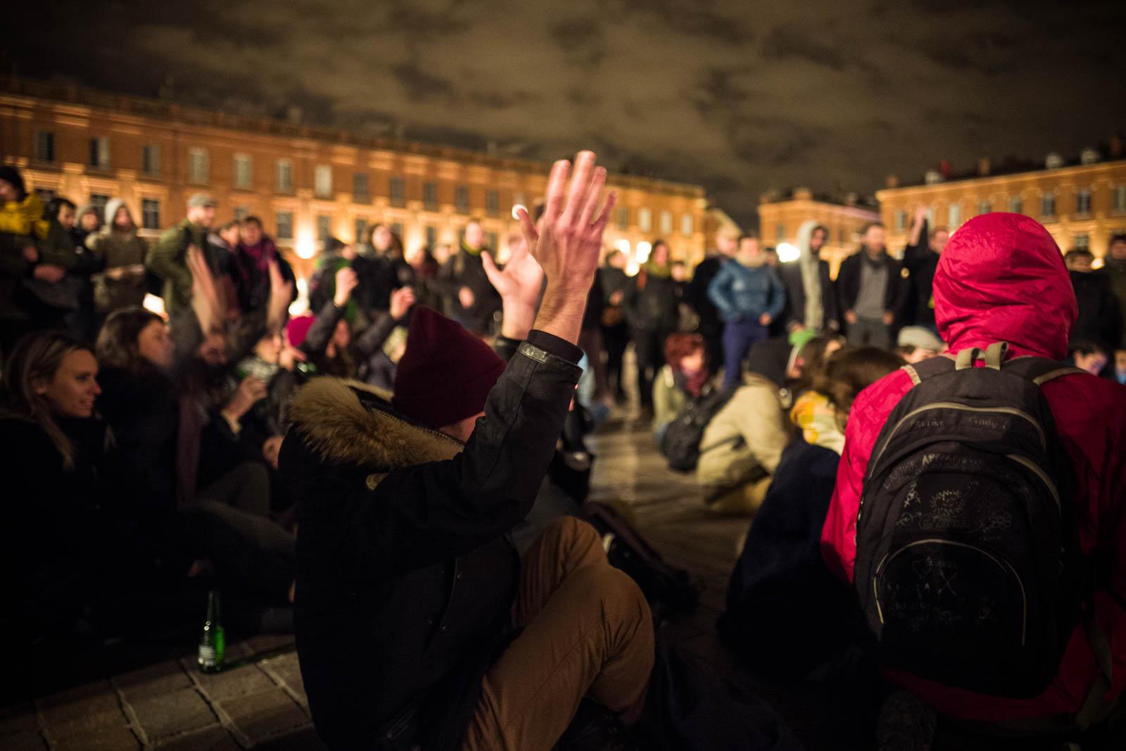 Un homme léve les mains en signe d'approbation lors du rassemblement NUIT DEBOUT sur la place du Capitole. Depuis le 31 mars des personnes se sont installées sur différentes grandes places dans des villes de l'hexagone la nuit.  Ces rassemblements pacifiques, appellés NUIT DEBOUT sont ouverts et populaires, ils visent à réinvestir l'espace public pour échanger, débattre et construire, la Place du Capitole est occupée depuis le 5 avril. 8/04/2016, Toulouse-France.
