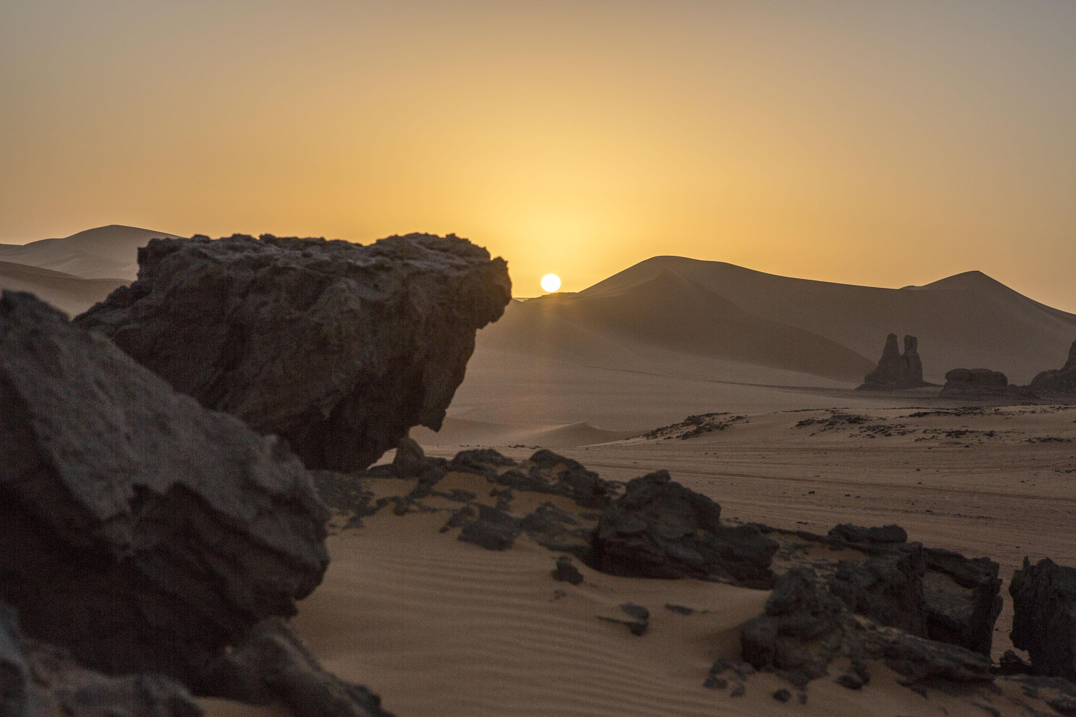 Sunrise in the Tadrart. The Tadrart (200 km southeast of Djanet) is located in the south of the Tassili N'Ajjer National Park and is part of one of the most beautiful deserts in the world but above all in the central Sahara.From huge canyons to cliffs carved with rocky peaks of various shapes mix with dunes of colored sand with yellow and red reflections. La Tadrart, Algeria-February 9, 2017.Lever de soleil dans la Tadrart. La Tadrart (200 km au sud-est de Djanet) se situe dans le sud du Parc National du Tassili N'Ajjer et il fait partie d'un des plus beau désert au monde mais avant tout du Sahara central. D'immenses canyons aux falaises sculptées avec de pitons rocheux aux formes les plus diverses  se mélangent avec des dunes de sable coloré aux reflets jaune et rouge. La Tadrart, Algérie-9 février 2017.