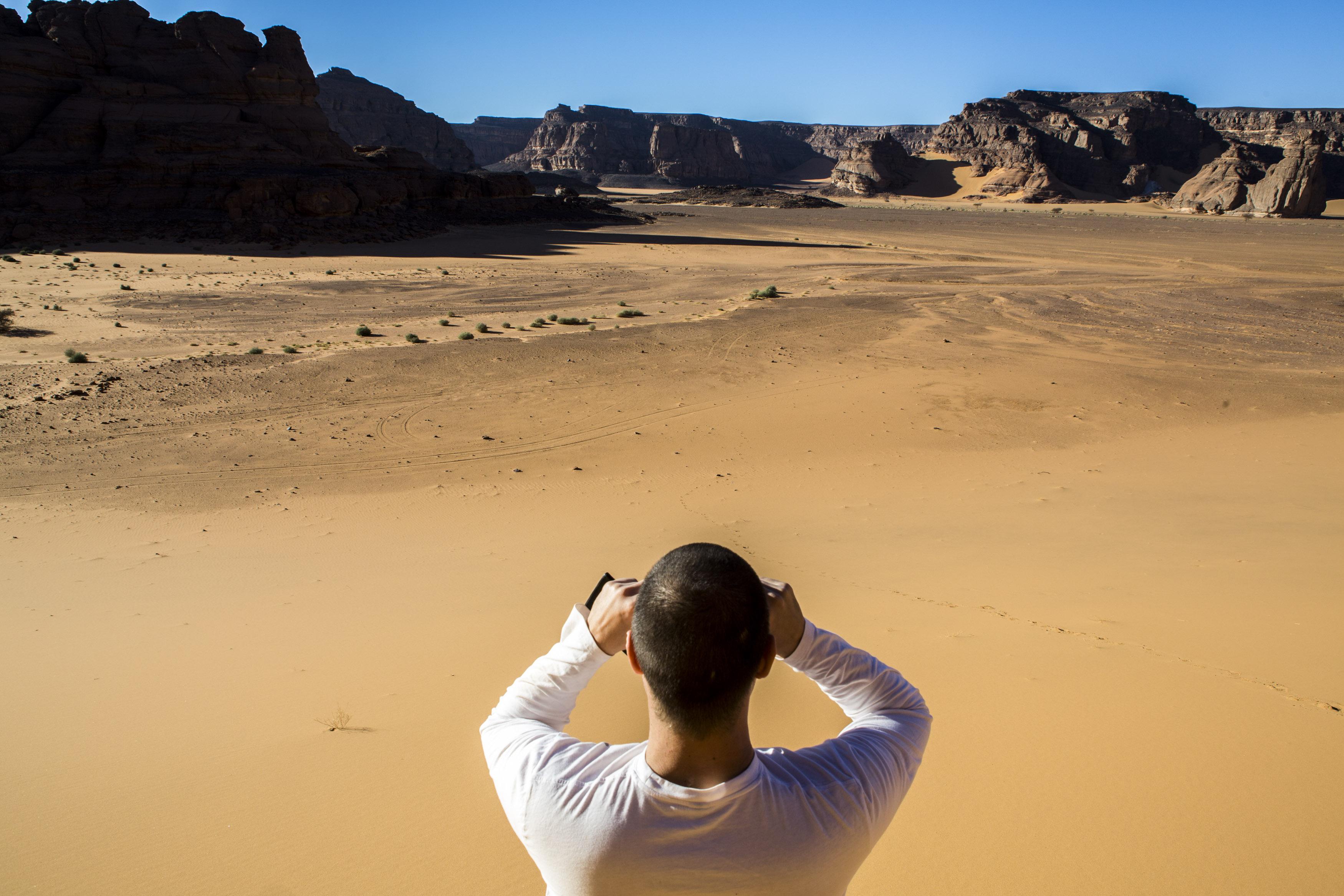 One man is looking at the landscape in the Tadrart.The Tadrart (200 km southeast of Djanet) is located in the south of the Tassili N'Ajjer National Park and is part of one of the most beautiful desert in the world but above all the central Sahara.From huge canyons to cliffs carved with rocky peaks of various shapes mix with dunes of colored sand with yellow and red reflections. The Tadrart, Algeria-February 5, 2017. Un homme de dos regarde le paysage de la Tadrart. La Tadrart (200 km au sud-est de Djanet) se situe dans le sud du Parc National du Tassili N'Ajjer et il fait partie d'un des plus beau désert au monde mais avant tout du Sahara central. D'immenses canyons aux falaises sculptées avec de pitons rocheux aux formes les plus diverses  se mélangent avec des dunes de sable coloré aux reflets jaune et rouge. La Tadrart,, Algérie-5 février 2017.