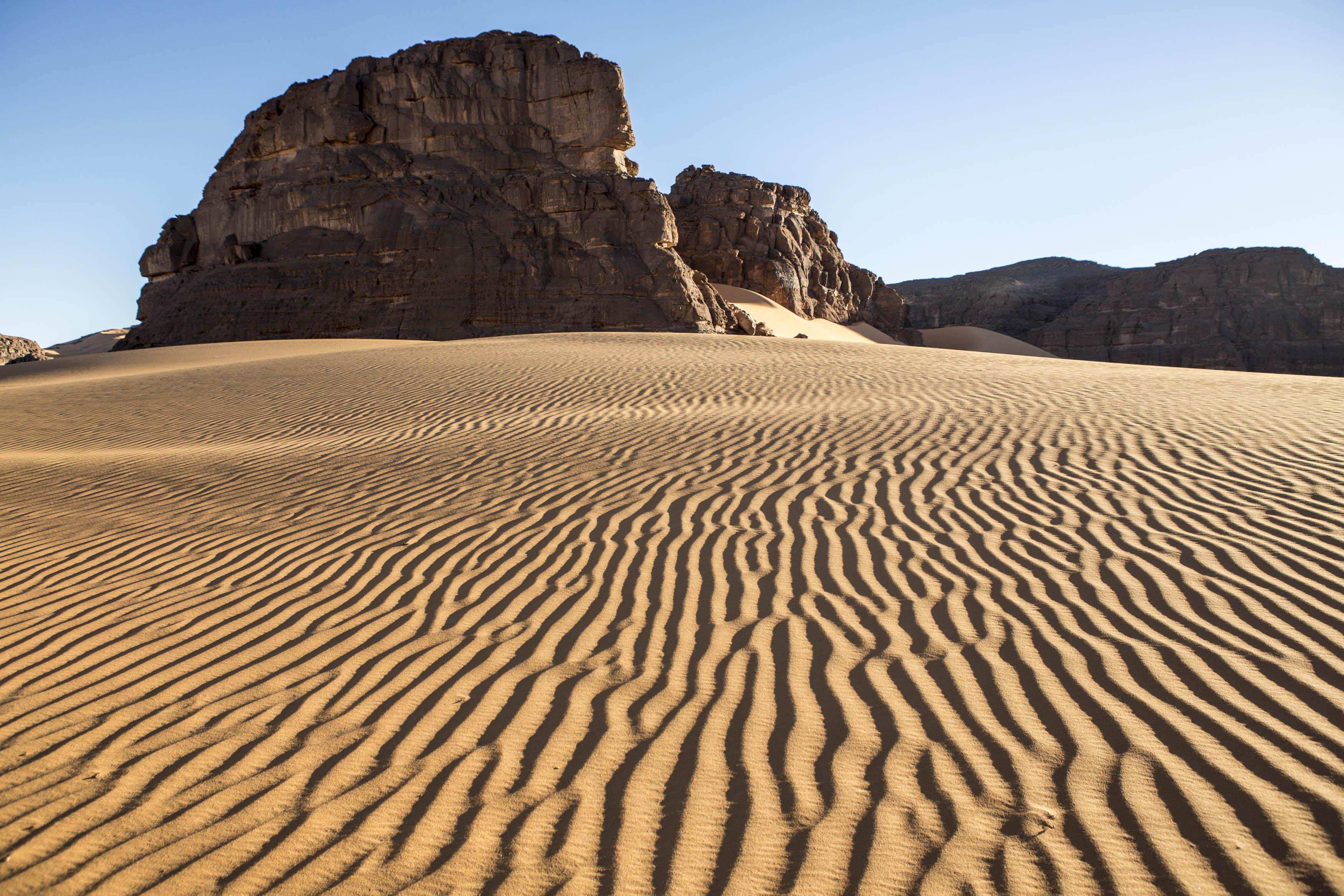 Landscape of the Tadrart.The Tadrart (200 km southeast of Djanet) is located in the south of the Tassili N'Ajjer National Park and is part of one of the most beautiful desert in the world but above all the central Sahara.From huge canyons to cliffs carved with rocky peaks of various shapes mix with dunes of colored sand with yellow and red reflections. The Tadrart, Algeria-February 6, 2017. Paysage de la Tadrart. La Tadrart (200 km au sud-est de Djanet) se situe dans le sud du Parc National du Tassili N'Ajjer et il fait partie d'un des plus beau désert au monde mais avant tout du Sahara central. D'immenses canyons aux falaises sculptées avec de pitons rocheux aux formes les plus diverses  se mélangent avec des dunes de sable coloré aux reflets jaune et rouge. La Tadrart,, Algérie-6 février 2017.