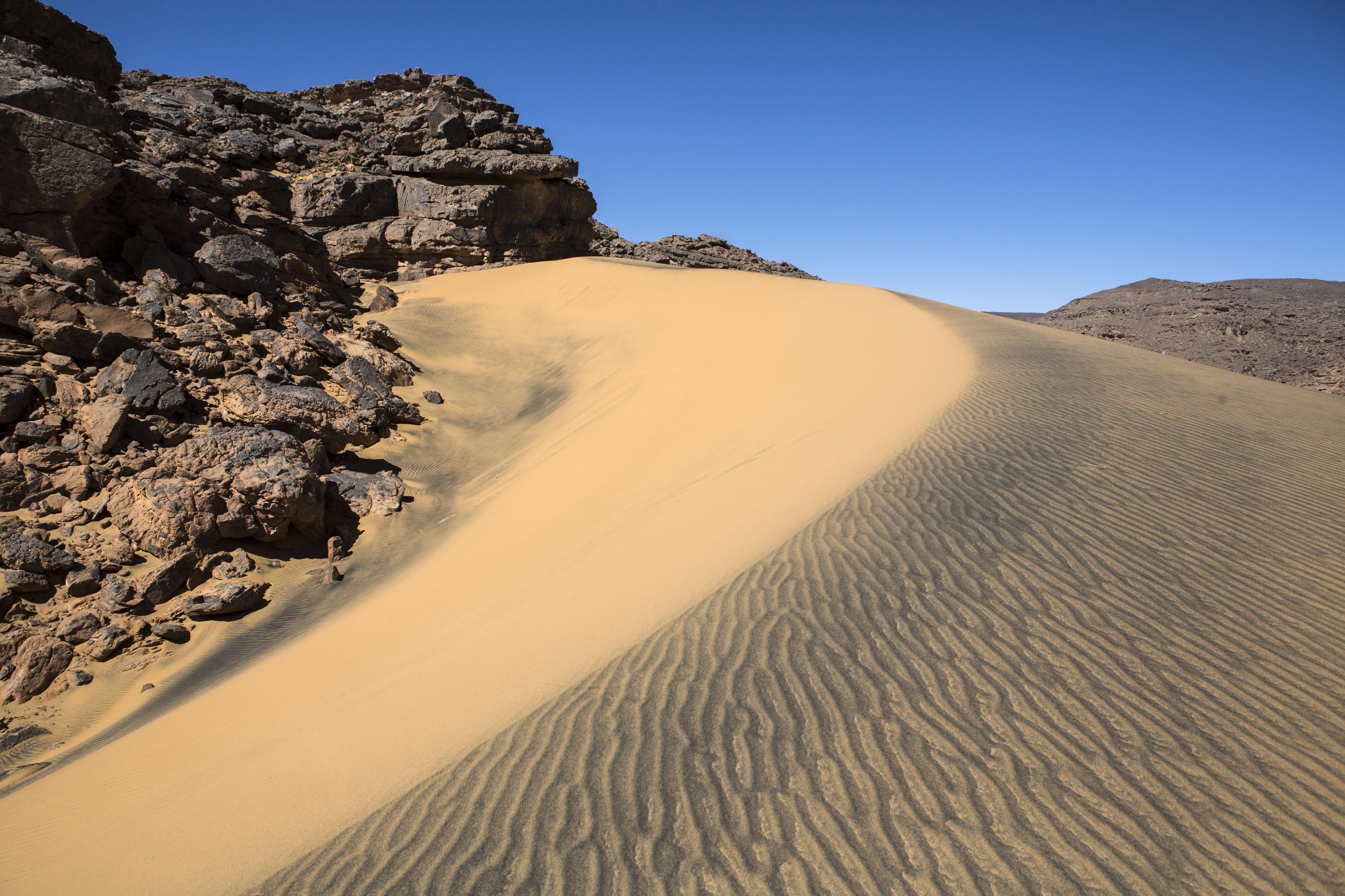 Landscape of the Tadrart.The Tadrart (200 km southeast of Djanet) is located in the south of the Tassili N'Ajjer National Park and is part of one of the most beautiful desert in the world but above all the central Sahara.From huge canyons to cliffs carved with rocky peaks of various shapes mix with dunes of colored sand with yellow and red reflections. The Tadrart, Algeria-February 5, 2017. Paysage de la Tadrart. La Tadrart (200 km au sud-est de Djanet) se situe dans le sud du Parc National du Tassili N'Ajjer et il fait partie d'un des plus beau désert au monde mais avant tout du Sahara central. D'immenses canyons aux falaises sculptées avec de pitons rocheux aux formes les plus diverses  se mélangent avec des dunes de sable coloré aux reflets jaune et rouge. La Tadrart,, Algérie-5 février 2017.