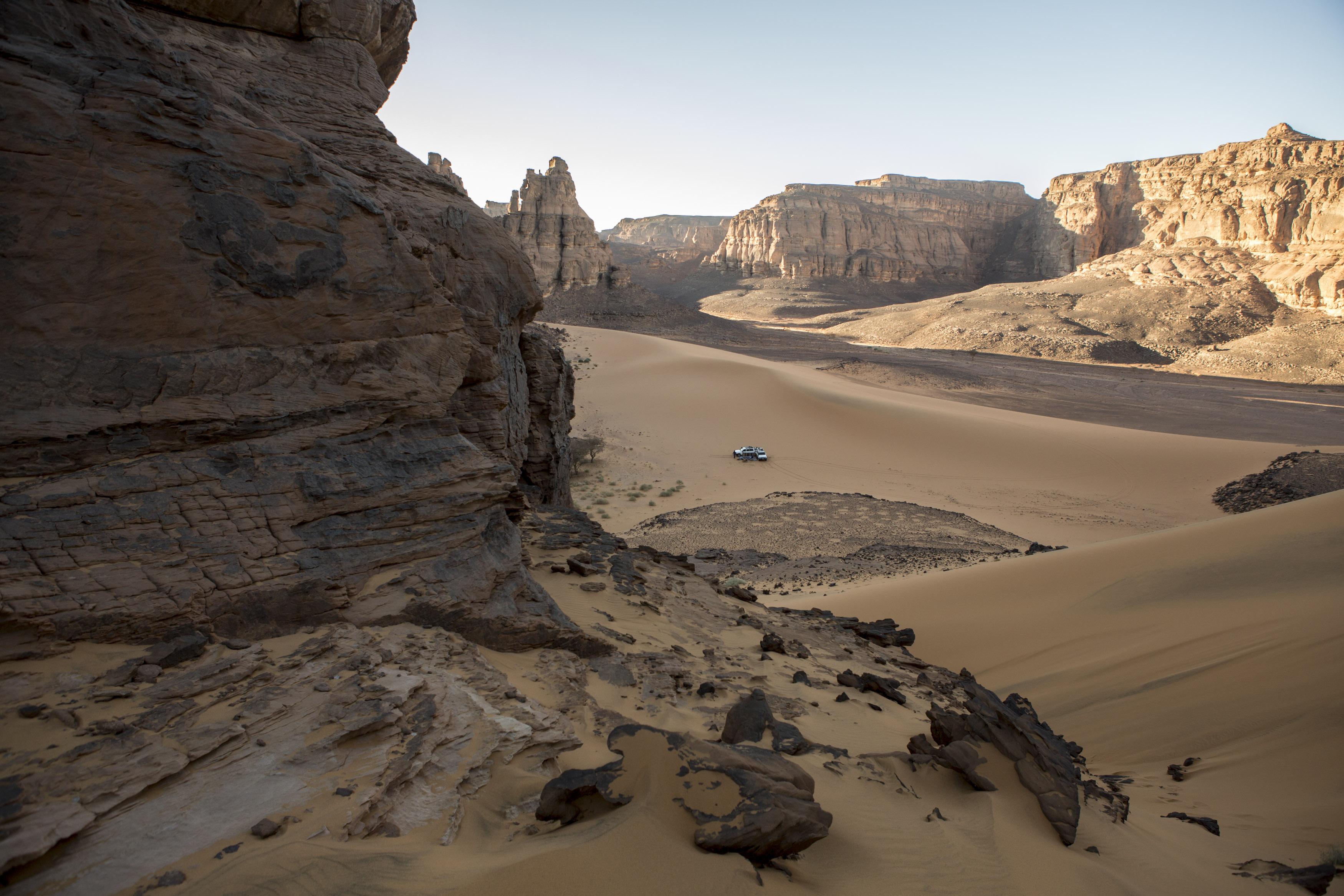 Two crews with their 4x4 vehicles are preparing for the evening bivouac in the Tadrart. La Tadrart (200 km southeast)The Tadrart (200 km southeast of Djanet) is located in the south of the Tassili N'Ajjer National Park and is part of one of the most beautiful desert in the world but above all the central Sahara.From huge canyons to cliffs carved with rocky peaks of various shapes mix with dunes of colored sand with yellow and red reflections. The Tadrart, Algeria-February 5, 2017. Deux équipages avec leur véhicules 4x4 se préparent pour le bivouac du soir dans la Tadrart. La Tadrart (200 km au sud-est de Djanet) se situe dans le sud du Parc National du Tassili N'Ajjer et il fait partie d'un des plus beau désert au monde mais avant tout du Sahara central. D'immenses canyons aux falaises sculptées avec de pitons rocheux aux formes les plus diverses  se mélangent avec des dunes de sable coloré aux reflets jaune et rouge. La Tadrart,, Algérie-5 février 2017.