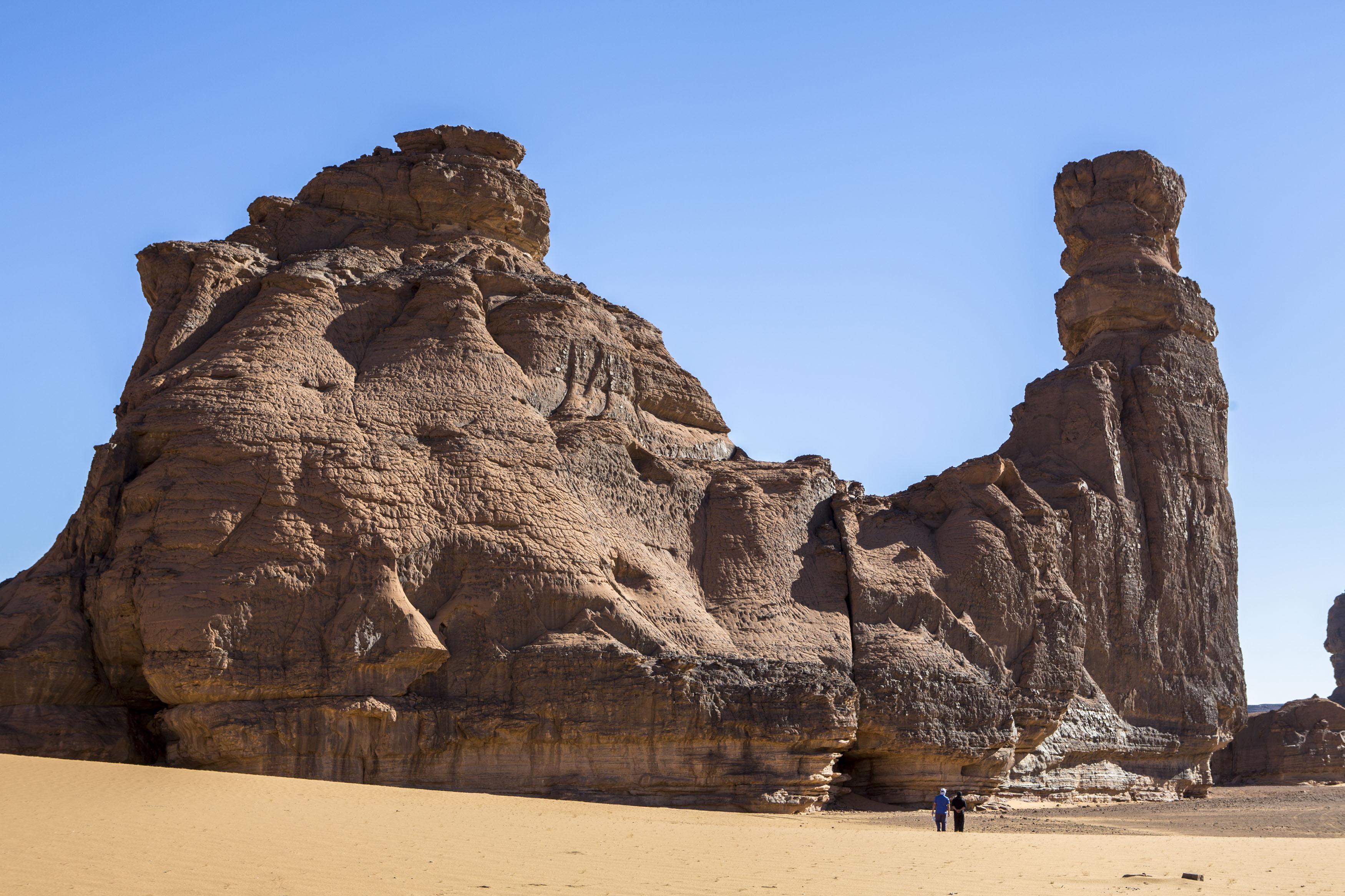 Tourists are walking in the Tadrart.The Tadrart (200 km southeast of Djanet) is located in the south of the Tassili N'Ajjer National Park and is part of one of the most beautiful desert in the world but above all the central Sahara.From huge canyons to cliffs carved with rocky peaks of various shapes mix with dunes of colored sand with yellow and red reflections. The Tadrart, Algeria-February 6, 2017. Des touristes marchent dans la Tadrart. La Tadrart (200 km au sud-est de Djanet) se situe dans le sud du Parc National du Tassili N'Ajjer et il fait partie d'un des plus beau désert au monde mais avant tout du Sahara central. D'immenses canyons aux falaises sculptées avec de pitons rocheux aux formes les plus diverses  se mélangent avec des dunes de sable coloré aux reflets jaune et rouge. La Tadrart,, Algérie-6 février 2017.
