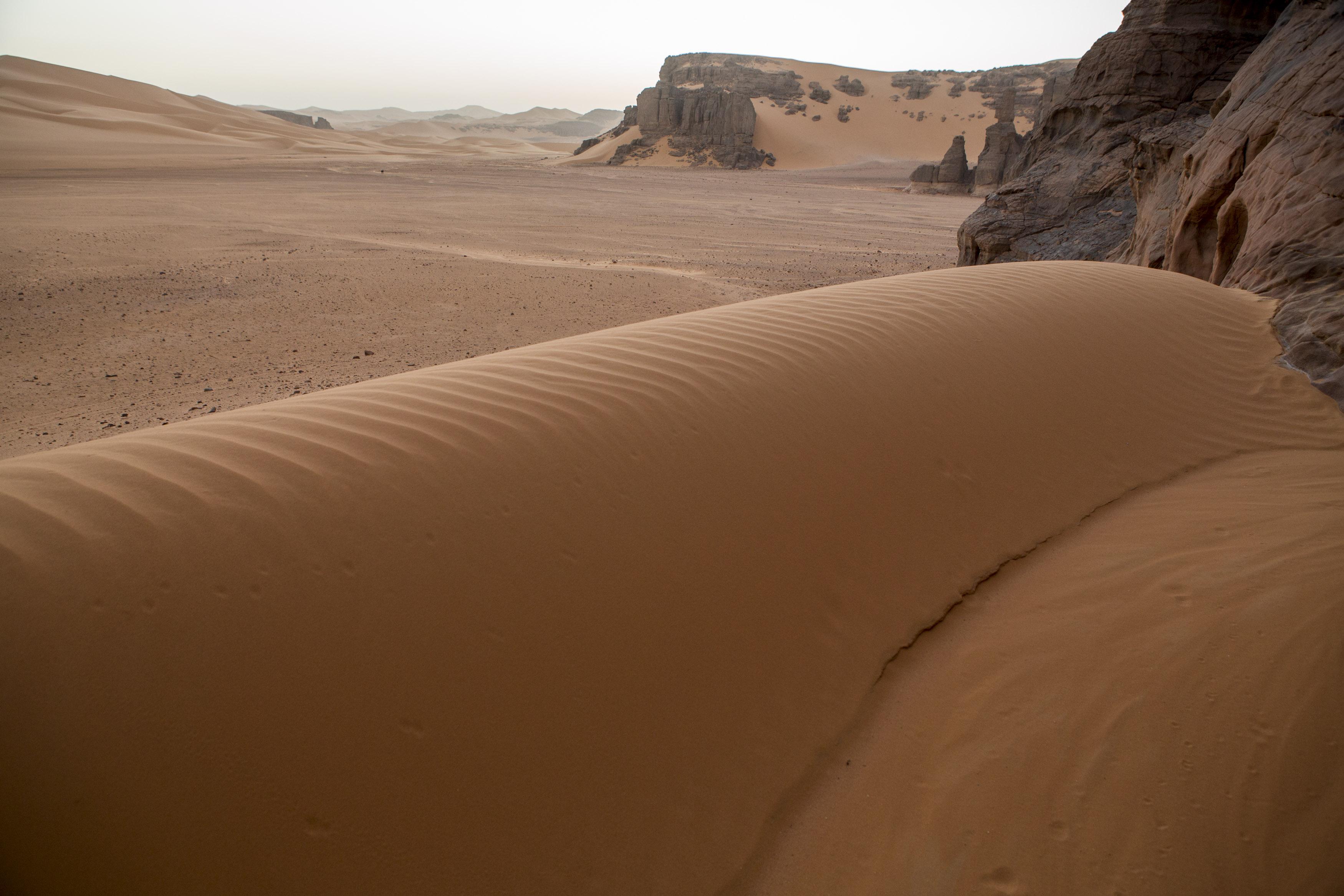 Landscape of the Tadrart.The Tadrart (200 km southeast of Djanet) is located in the south of the Tassili N'Ajjer National Park and is part of one of the most beautiful desert in the world but above all the central Sahara.From huge canyons to cliffs carved with rocky peaks of various shapes mix with dunes of colored sand with yellow and red reflections. The Tadrart, Algeria-February 7, 2017. Paysage de la Tadrart. La Tadrart (200 km au sud-est de Djanet) se situe dans le sud du Parc National du Tassili N'Ajjer et il fait partie d'un des plus beau désert au monde mais avant tout du Sahara central. D'immenses canyons aux falaises sculptées avec de pitons rocheux aux formes les plus diverses  se mélangent avec des dunes de sable coloré aux reflets jaune et rouge. La Tadrart, Algérie-7 février 2017.