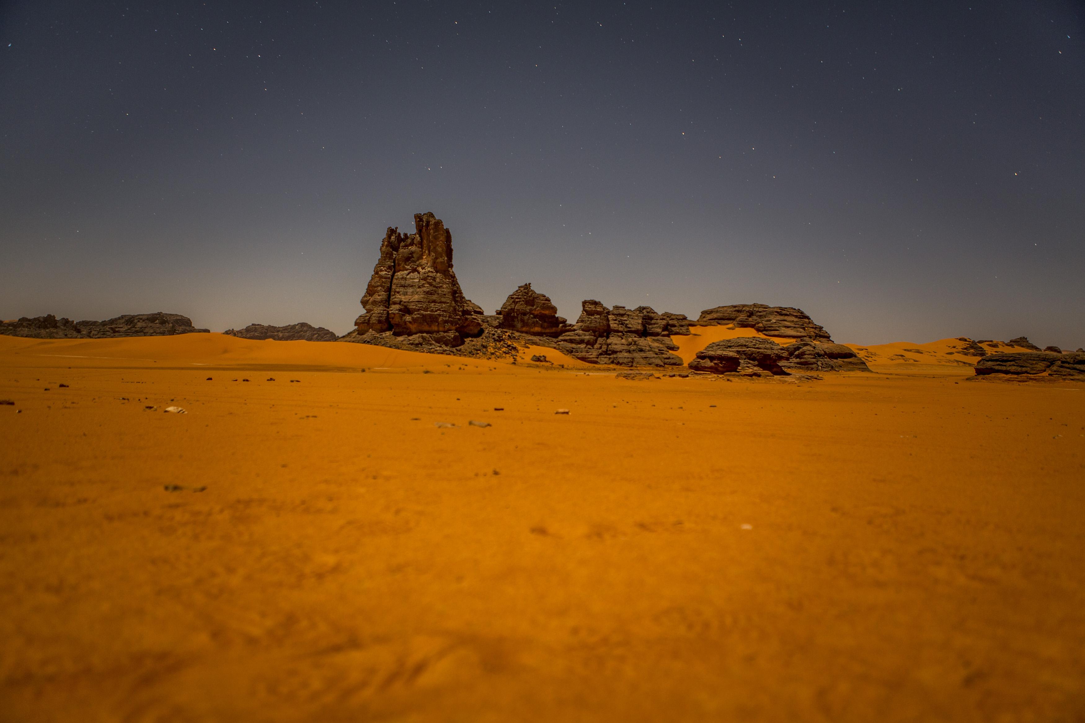 Night landscape in the Tadrart. The Tadrart (200 km southeast of Djanet) is located in the south of the Tassili N'Ajjer National Park and is part of one of the most beautiful deserts in the world but above all in the central Sahara.From huge canyons to cliffs carved with rocky peaks of various shapes mix with dunes of colored sand with yellow and red reflections. La Tadrart, Algeria-February 9, 2017.Paysage de nuit dans la Tadrart. La Tadrart (200 km au sud-est de Djanet) se situe dans le sud du Parc National du Tassili N'Ajjer et il fait partie d'un des plus beau désert au monde mais avant tout du Sahara central. D'immenses canyons aux falaises sculptées avec de pitons rocheux aux formes les plus diverses  se mélangent avec des dunes de sable coloré aux reflets jaune et rouge. La Tadrart, Algérie-9 février 2017.