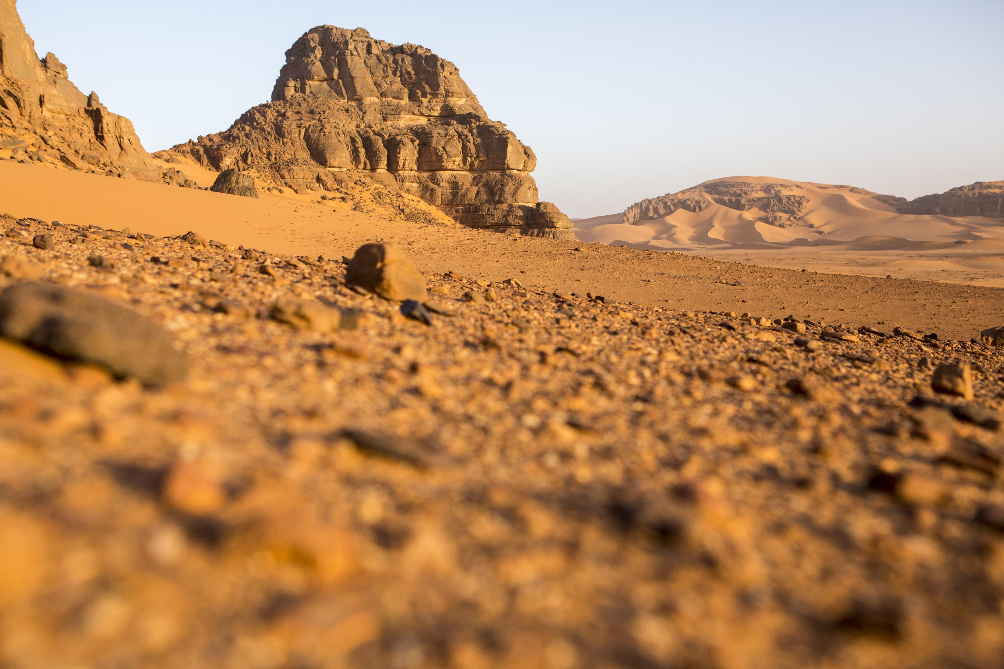 Sunrise in the Tadrart. The Tadrart (200 km southeast of Djanet) is located in the south of the Tassili N'Ajjer National Park and is part of one of the most beautiful deserts in the world but above all in the central Sahara.From huge canyons to cliffs carved with rocky peaks of various shapes mix with dunes of colored sand with yellow and red reflections. La Tadrart, Algeria-February 7, 2017.Lever de soleil dans la Tadrart. La Tadrart (200 km au sud-est de Djanet) se situe dans le sud du Parc National du Tassili N'Ajjer et il fait partie d'un des plus beau désert au monde mais avant tout du Sahara central. D'immenses canyons aux falaises sculptées avec de pitons rocheux aux formes les plus diverses  se mélangent avec des dunes de sable coloré aux reflets jaune et rouge. La Tadrart, Algérie-7 février 2017.