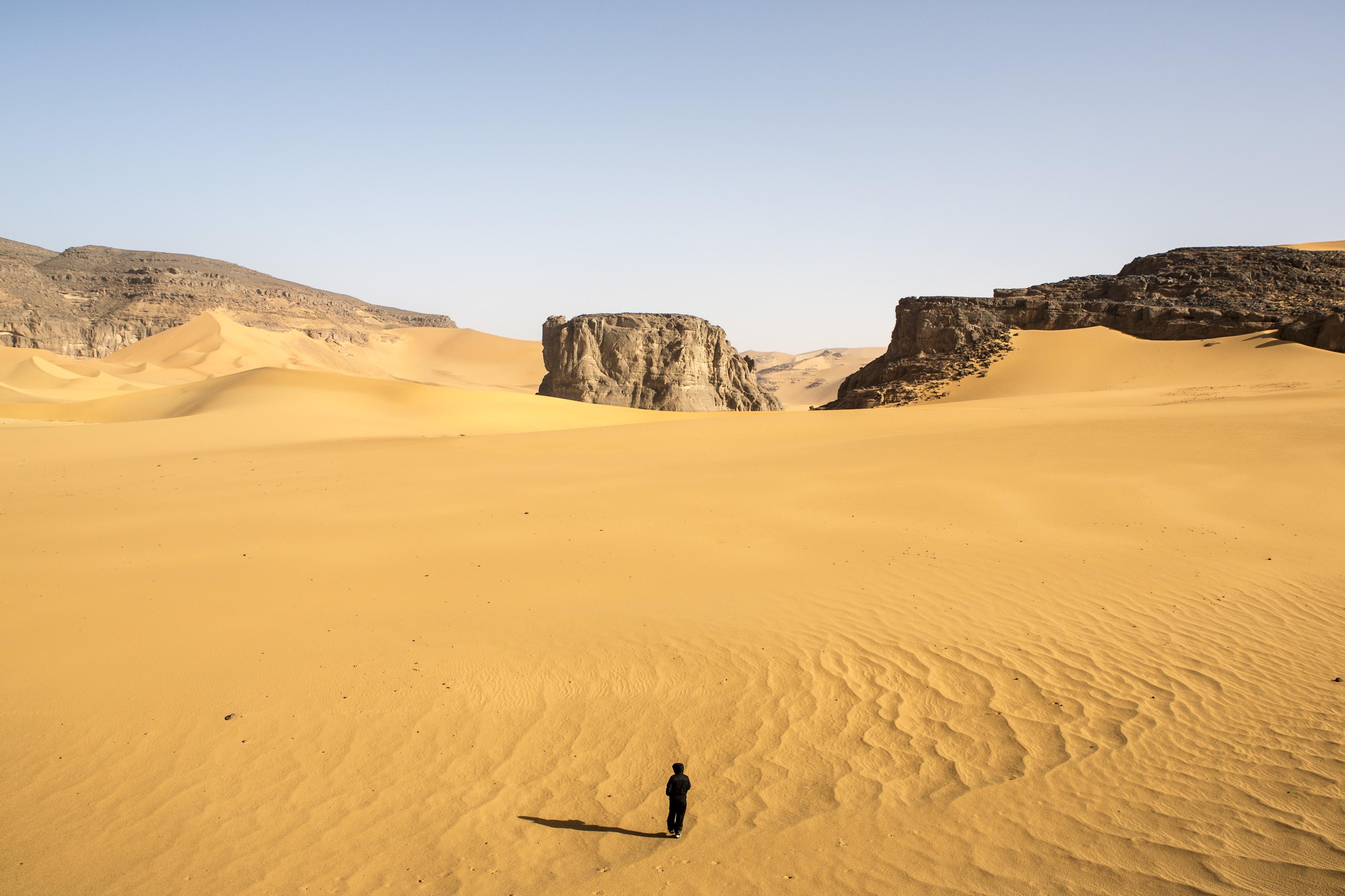One man is walking alone in the Tadrart.The Tadrart (200 km southeast of Djanet) is located in the south of the Tassili N'Ajjer National Park and is part of one of the most beautiful desert in the world but above all the central Sahara.From huge canyons to cliffs carved with rocky peaks of various shapes mix with dunes of colored sand with yellow and red reflections. The Tadrart, Algeria-February 8, 2017. Un homme marche seul dans la Tadrart. La Tadrart (200 km au sud-est de Djanet) se situe dans le sud du Parc National du Tassili N'Ajjer et il fait partie d'un des plus beau désert au monde mais avant tout du Sahara central. D'immenses canyons aux falaises sculptées avec de pitons rocheux aux formes les plus diverses  se mélangent avec des dunes de sable coloré aux reflets jaune et rouge. La Tadrart, Algérie-8 février 2017.