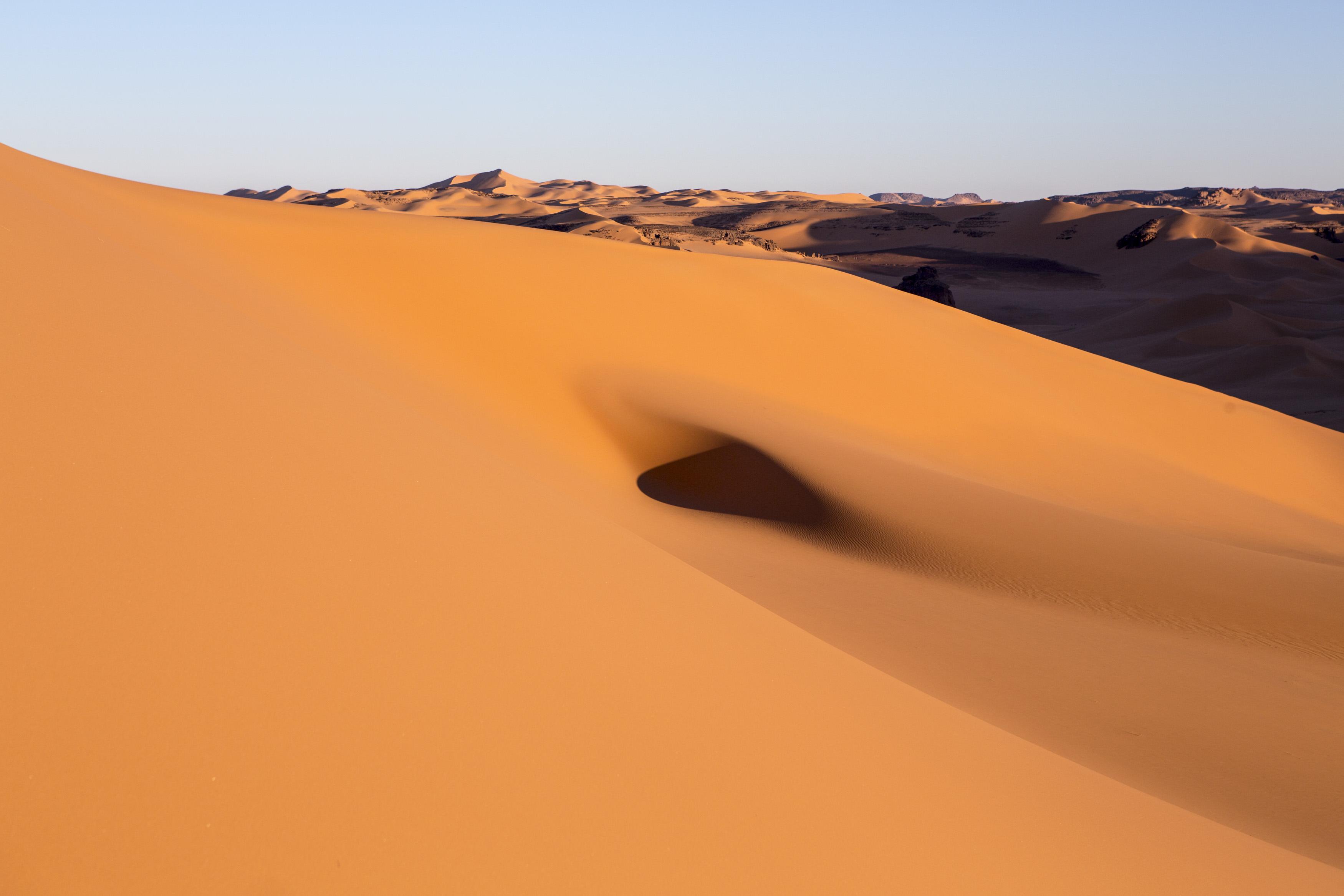 Landscape of the Tadrart.The Tadrart (200 km southeast of Djanet) is located in the south of the Tassili N'Ajjer National Park and is part of one of the most beautiful desert in the world but above all the central Sahara.From huge canyons to cliffs carved with rocky peaks of various shapes mix with dunes of colored sand with yellow and red reflections. The Tadrart, Algeria-February 6, 2017. Paysage de la Tadrart. La Tadrart (200 km au sud-est de Djanet) se situe dans le sud du Parc National du Tassili N'Ajjer et il fait partie d'un des plus beau désert au monde mais avant tout du Sahara central. D'immenses canyons aux falaises sculptées avec de pitons rocheux aux formes les plus diverses  se mélangent avec des dunes de sable coloré aux reflets jaune et rouge. La Tadrart, Algérie-6 février 2017.