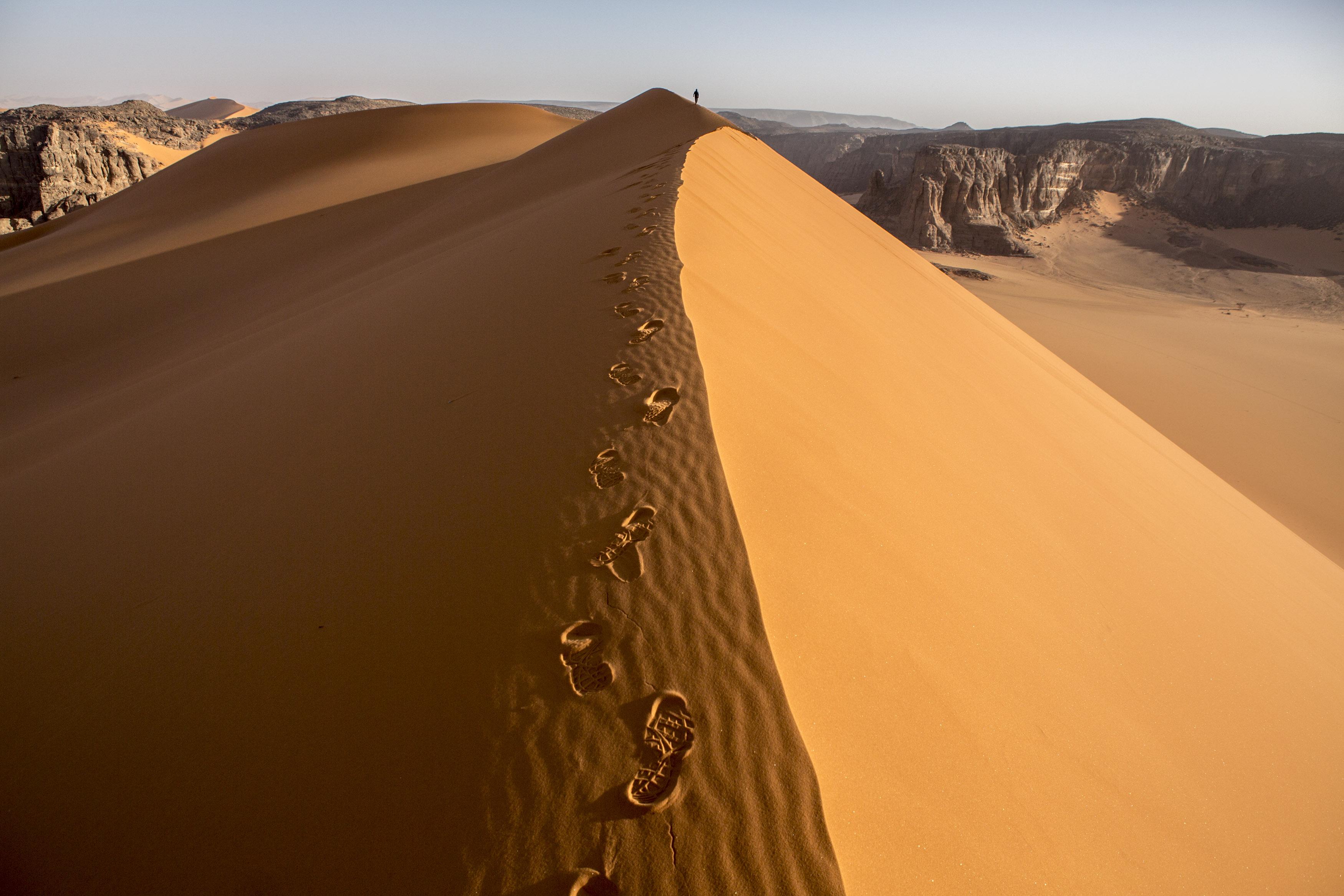 One man is walking alone on a dune in the Tadrart.The Tadrart (200 km southeast of Djanet) is located in the south of the Tassili N'Ajjer National Park and is part of one of the most beautiful desert in the world but above all the central Sahara.From huge canyons to cliffs carved with rocky peaks of various shapes mix with dunes of colored sand with yellow and red reflections. The Tadrart, Algeria-February 8, 2017. Un homme marche seul sur une grande dune dans la Tadrart. La Tadrart (200 km au sud-est de Djanet) se situe dans le sud du Parc National du Tassili N'Ajjer et il fait partie d'un des plus beau désert au monde mais avant tout du Sahara central. D'immenses canyons aux falaises sculptées avec de pitons rocheux aux formes les plus diverses  se mélangent avec des dunes de sable coloré aux reflets jaune et rouge. La Tadrart, Algérie-8 février 2017.