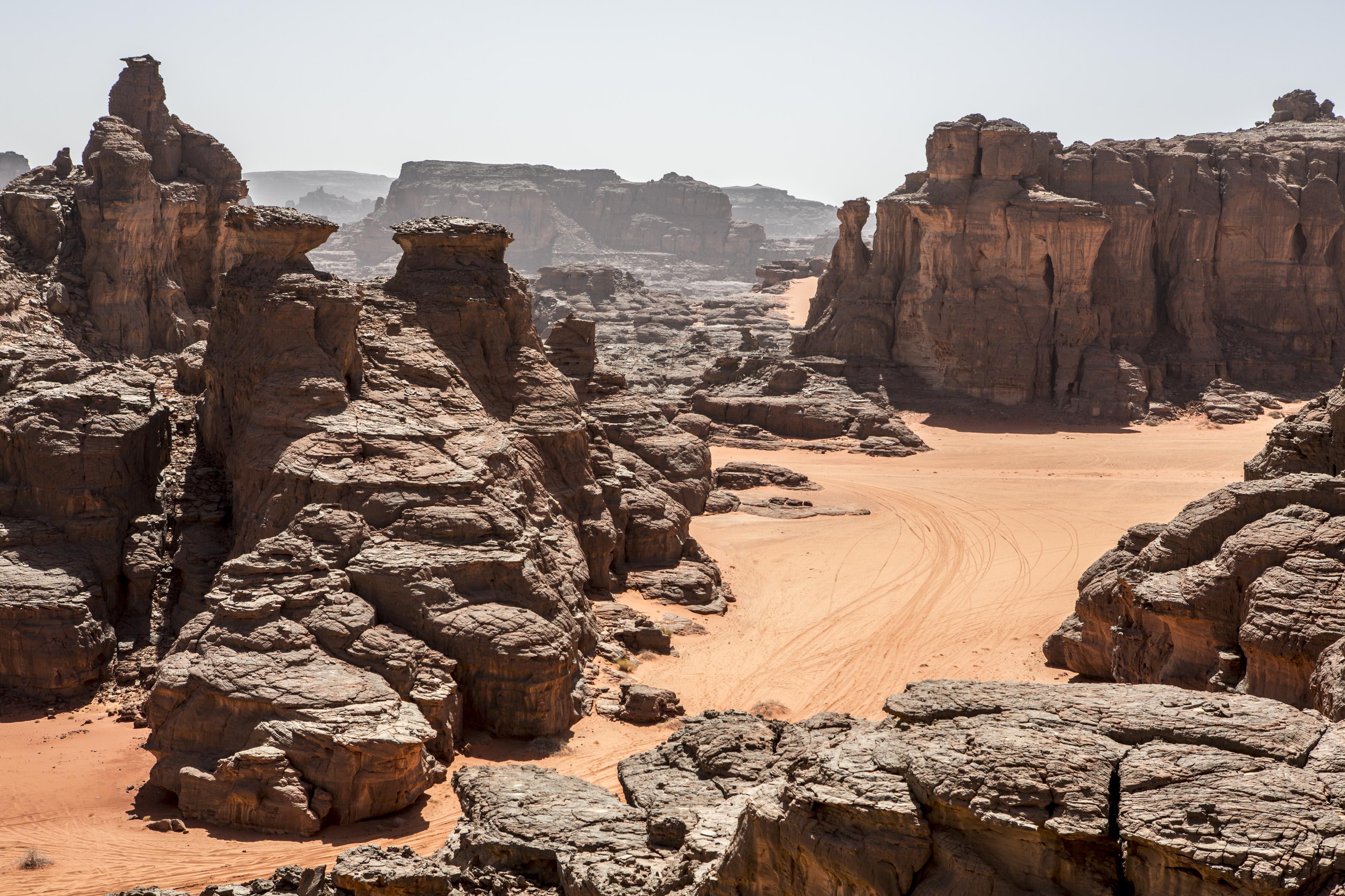 Landscape of the Tadrart.The Tadrart (200 km southeast of Djanet) is located in the south of the Tassili N'Ajjer National Park and is part of one of the most beautiful desert in the world but above all the central Sahara.From huge canyons to cliffs carved with rocky peaks of various shapes mix with dunes of colored sand with yellow and red reflections. The Tadrart, Algeria-February 9, 2017. Paysage de la Tadrart. La Tadrart (200 km au sud-est de Djanet) se situe dans le sud du Parc National du Tassili N'Ajjer et il fait partie d'un des plus beau désert au monde mais avant tout du Sahara central. D'immenses canyons aux falaises sculptées avec de pitons rocheux aux formes les plus diverses  se mélangent avec des dunes de sable coloré aux reflets jaune et rouge. La Tadrart, Algérie-9 février 2017.