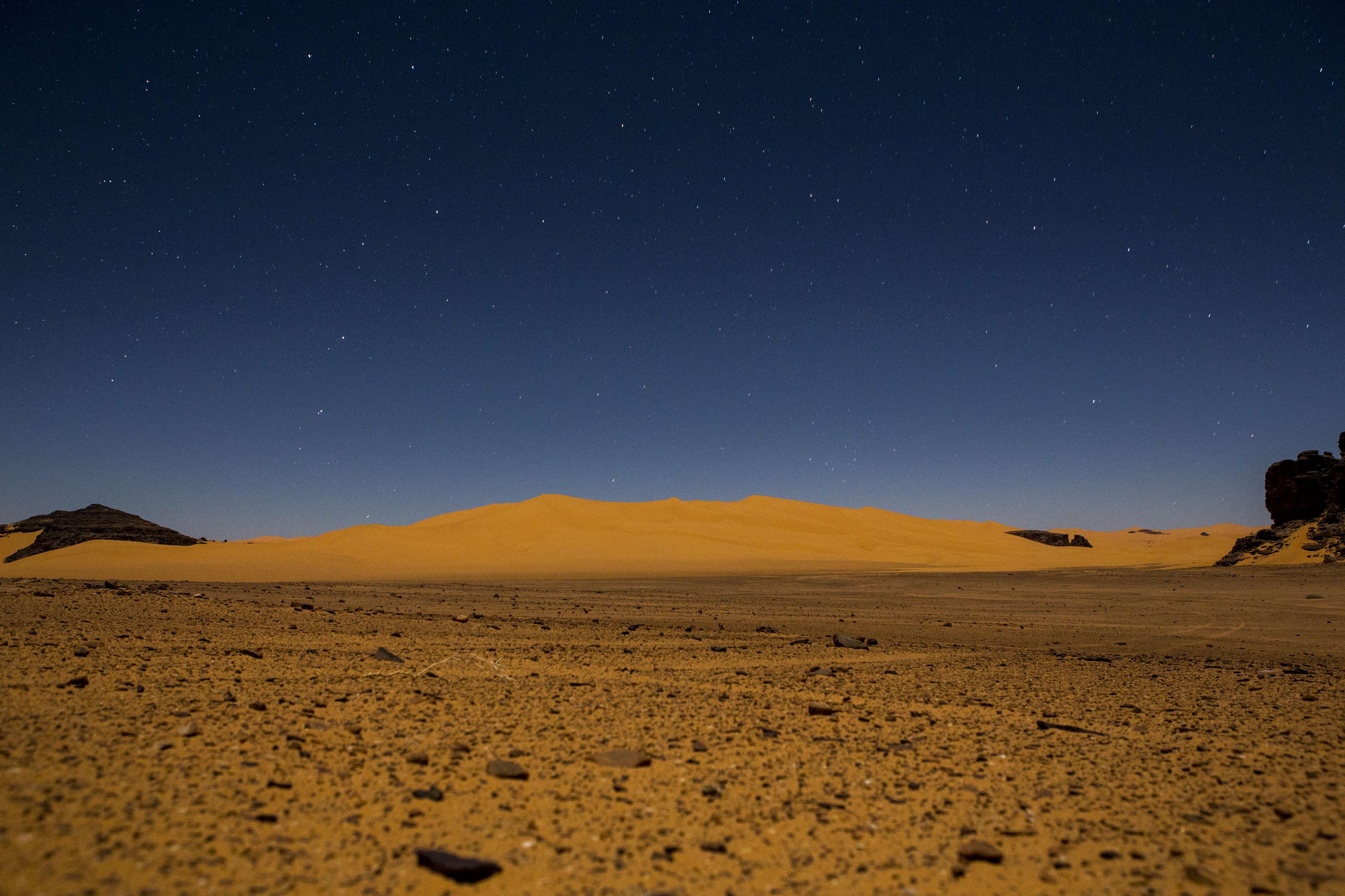 Night landscape in the Tadrart. The Tadrart (200 km southeast of Djanet) is located in the south of the Tassili N'Ajjer National Park and is part of one of the most beautiful deserts in the world but above all in the central Sahara.From huge canyons to cliffs carved with rocky peaks of various shapes mix with dunes of colored sand with yellow and red reflections. La Tadrart, Algeria-February 6, 2017.Paysage de nuit dans la Tadrart. La Tadrart (200 km au sud-est de Djanet) se situe dans le sud du Parc National du Tassili N'Ajjer et il fait partie d'un des plus beau désert au monde mais avant tout du Sahara central. D'immenses canyons aux falaises sculptées avec de pitons rocheux aux formes les plus diverses  se mélangent avec des dunes de sable coloré aux reflets jaune et rouge. La Tadrart, Algérie-6 février 2017.
